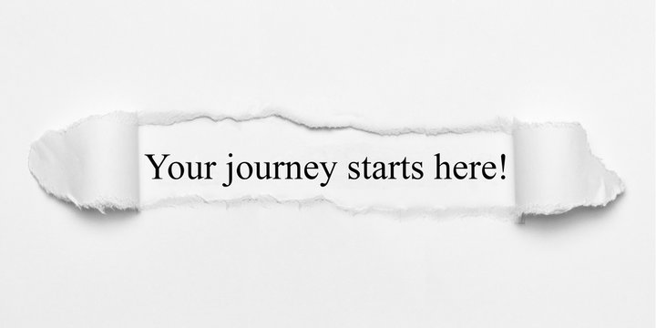 Your journey starts here! on white torn paper
