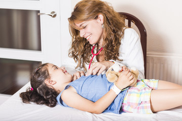 Little girl checked by friendly doctor with stethoscope