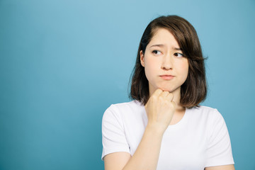 woman thinking on blue background.