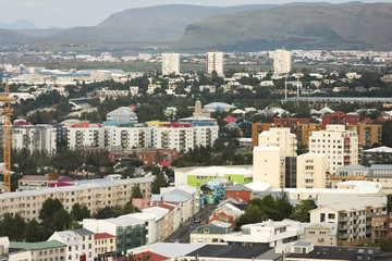 Beautiful aerial view of Reykjavik, Iceland with harbor and skyline mountains and scenery beyond the city, seen from the observation tower of Hallgrimskirkja Cathedral.