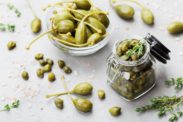 Mixed capers in jar and bowl on gray kitchen table from above.