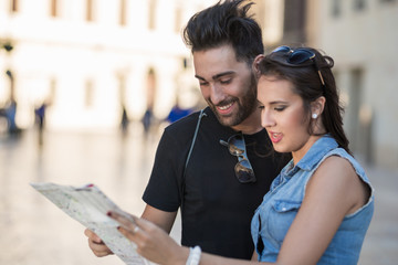 Happy tourist couple outside holding map