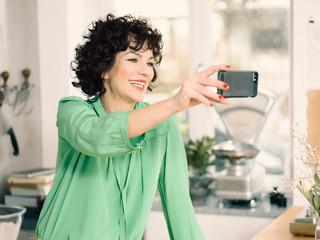 Woman in kitchen taking selfie smiling