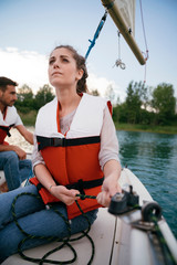 Woman on sailing boat, steering boat