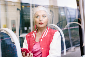 Mature woman in baseball jacket looking through window from bus