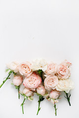 Flower composition with beige roses on white background. Flat lay, top view. Floral texture background.