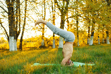 man practicing yoga in the park on the grass at sunset, Healthy lifestyle.