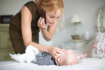 Mother changing baby son's nappy while using mobile phone