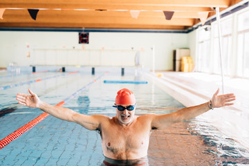 Senior man with open arms in swimming pool