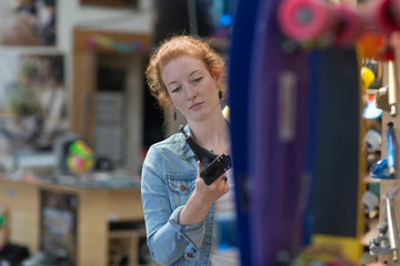 Woman working in skateboard shop, inspecting skateboard trucks
