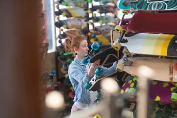 Woman working in skateboard shop, organising skateboard display