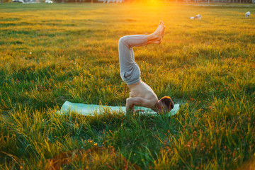 Man practicing yoga at sunset. Healthy lifestyle.