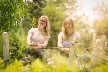 2 Freundinnen sitzen auf einer Holzbrücke - 2 Mädchen sitzen auf einer Brücke in der Sonne