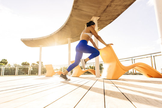 Young woman exercising outdoors, holding chair for balance, low angle view, South Point Park, Miami Beach, Florida, USA