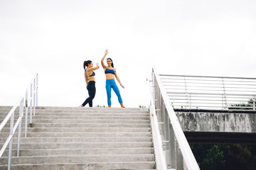 Two young women at top of steps, celebrating workout, South Point Park, Miami Beach, Florida, USA