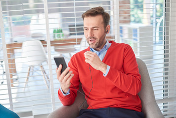 Man wearing earbuds looking at smartphone
