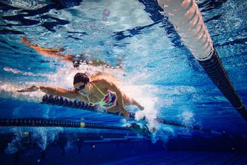 Woman swimming crawl stroke in swimming pool