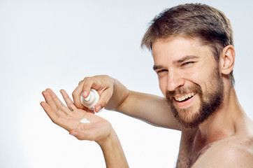 A young guy with a beard on a white isolated background is applying foam for shaving