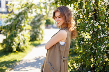 Beautiful young happy woman in fashionable clothes in the park