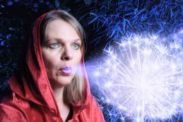 Frau mit roter Kapuze pustet auf leuchtende Blume