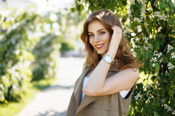 Beautiful happy woman with a smile in trendy clothes with a watch near blooming trees on a spring sunny day