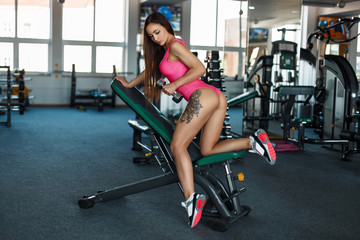 Sexy beautiful woman with a slim body with a tattoo trains with a dumbbell in the gym