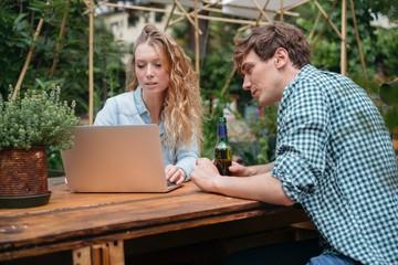 Couple with beer in garden using laptop