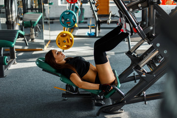 Beautiful young girl exercising on a sports foot-exerciser in the gym