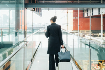 Businesswoman using mobile and pulling trolley luggage, Milan, Italy