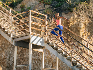 Young woman exercising, running up steps near beach, low angle view