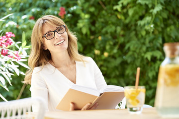 Confident mature woman portrait. Portrait of a laughing woman relaxing at home in the garden with a good book.