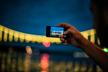 Man taking photo on smartphone at night