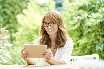Home office. Shot of a beautiful middle aged woman using laptop while sitting in the garden at home.