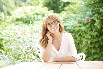 Enjoy my life. Outdoor portrait of a beautiful middle age woman sitting at garden terrace.