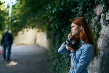 Beautiful young woman in a blue dress is walking along the boulevard in the city with her camera