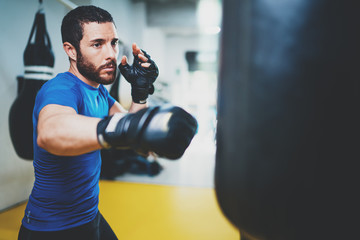 Concept of a healthy lifestyle.Young muscular man fighter practicing kicks with punching bag.Kick boxer boxing as exercise for the fight.Boxer hits punching bag.Horizontal.