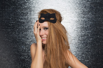 glamorous young woman at party with cat eye mask