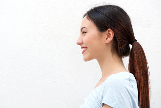 Side portrait of healthy young woman with long hair smiling