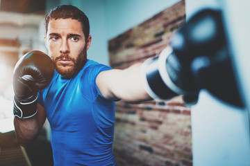 Young man athlete boxing workout in fitness gym on blurred background.Athletic man training hard.Kick boxing concept.Horizontal.