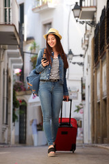 Full length woman walking on street with luggage holding mobile phone