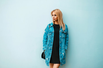 Fashionable beautiful young woman with a handbag in jeans clothes near a colored blue wall on the street