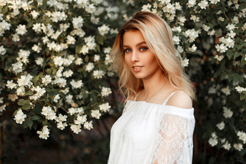 Portrait of a happy beautiful blonde woman in a vintage white lace dress near flowers
