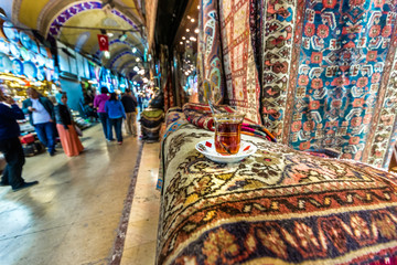 ISTANBUL, TURKEY- APRIL 17, 2017: Unidentified Tourists visiting and shopping in the Grand Bazaar in Istanbul.Interior of the Grand Bazaar with traditional Turkish tea on the foreground