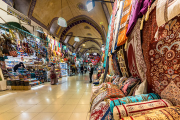 ISTANBUL, TURKEY- APRIL 17, 2017: Unidentified Tourists visiting and shopping in the Grand Bazaar in Istanbul.Interior of the Grand Bazaar with Turkish  rug and carpet on the front side.