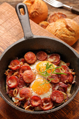Cooked egg and sausages on frying pan