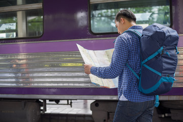 man traveler with backpacker look searching location at trainstation