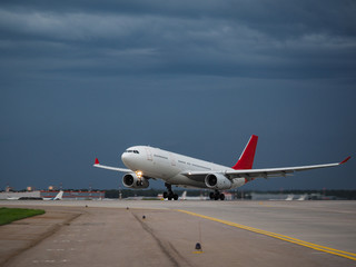 Airplane on the runway in the background of a rainy sky
