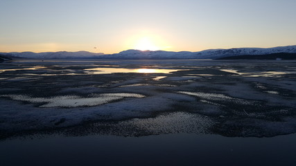 Midnight sun over an icy lake in Abisko