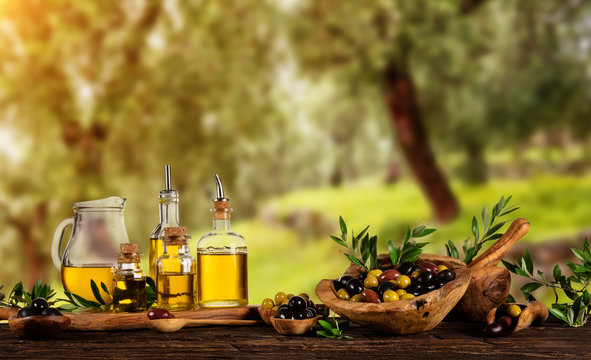 Freshly harvested olives berries in wood bowls and pressed oil in glass bottles