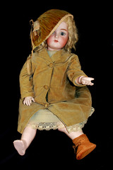 Antique Toy Doll on Black Background Missing a Shoe